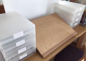 机の上に書類ケースを積んでいるイラスト