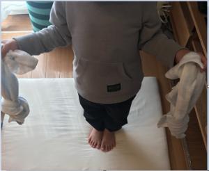 子どもが、結んだフェイスタオルを、右手、左手に持っている写真