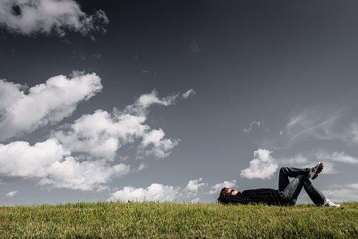 草原で寝転んでいる人の写真
